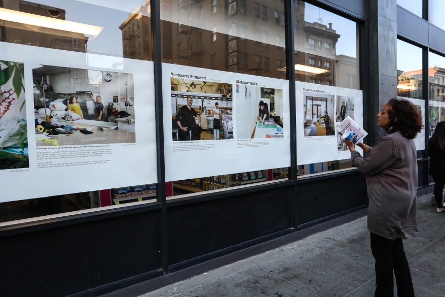 People stop to take in Janet Delaney's photography, which lines the windows of CVS for the 2 Blocks of Art walk.