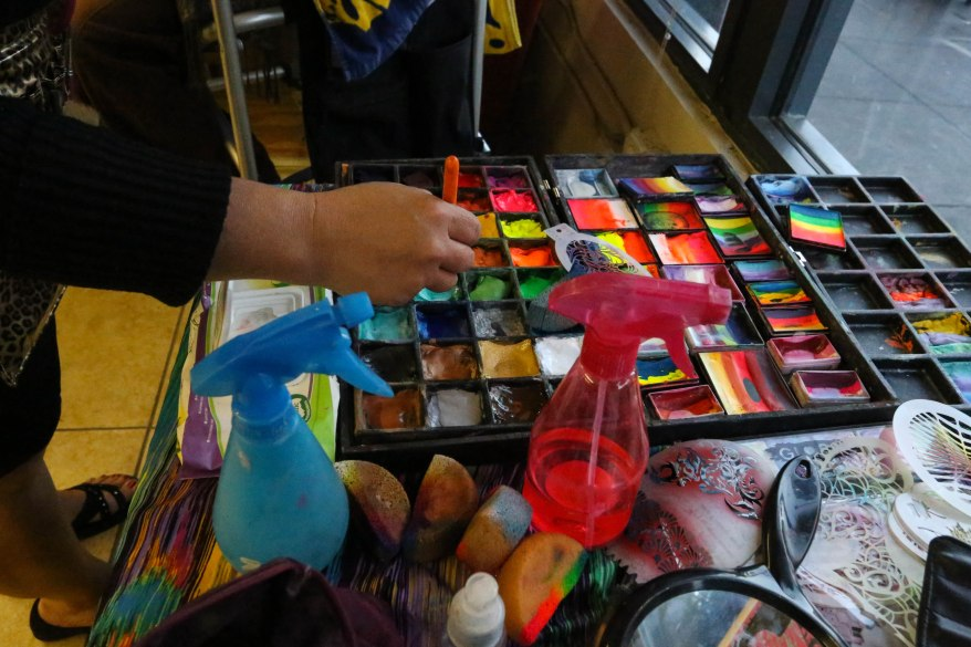 Jackie York, Make-up Your Mind, selects colors for her face painting design at the 6th Street Community Room.