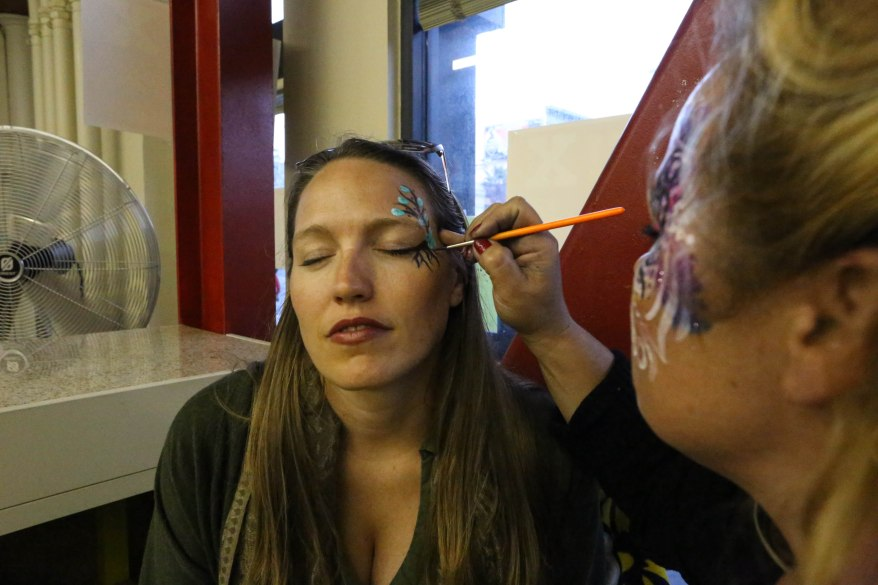 Tara Bush of Oakland gets her face painted at the 2 Blocks of Art walk by Jackie York of Make-up Your Mind.