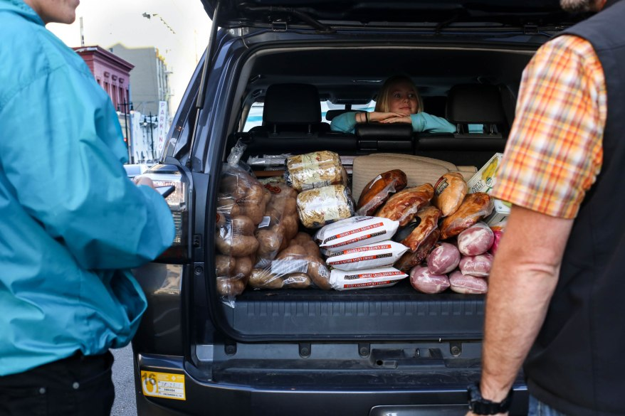 Curbside volunteers collect turkeys and other food donations for St. Anthony's Thanksgiving Day meals.