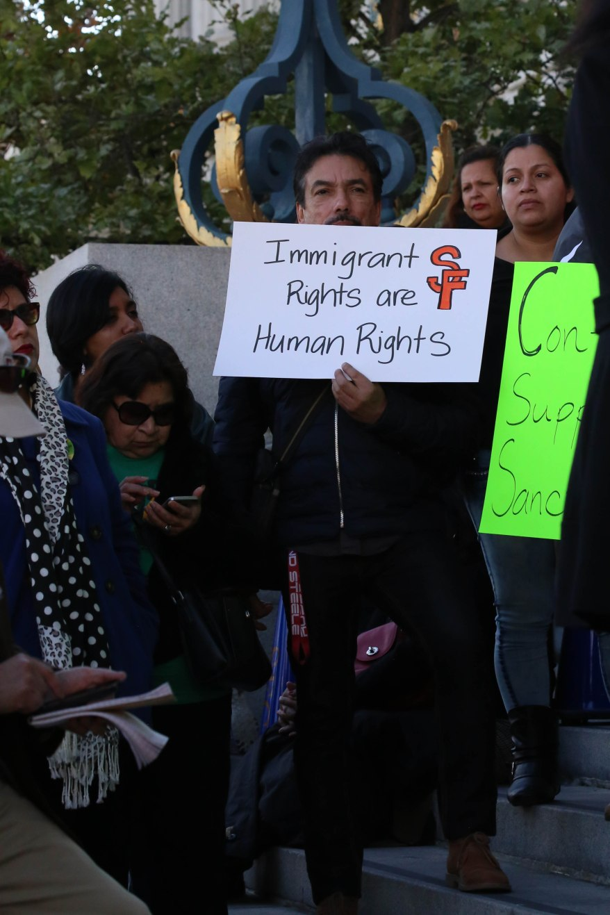 A demonstrator holds a sign in support of San Francisco's Sanctuary City policies for immigrants.